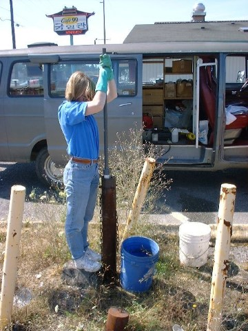 Scientist pulls water from a monitoring well that looks like a rusty pipe in the ground. She is beside a van in a parking lot.