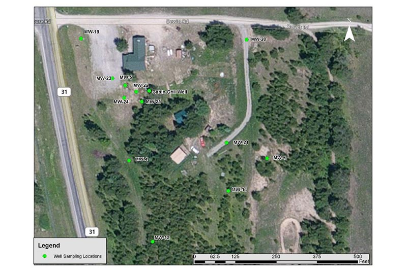 Photo of several buildings and roads with green dots labeled MW for Monitoring Well, indicating the sampling locations.