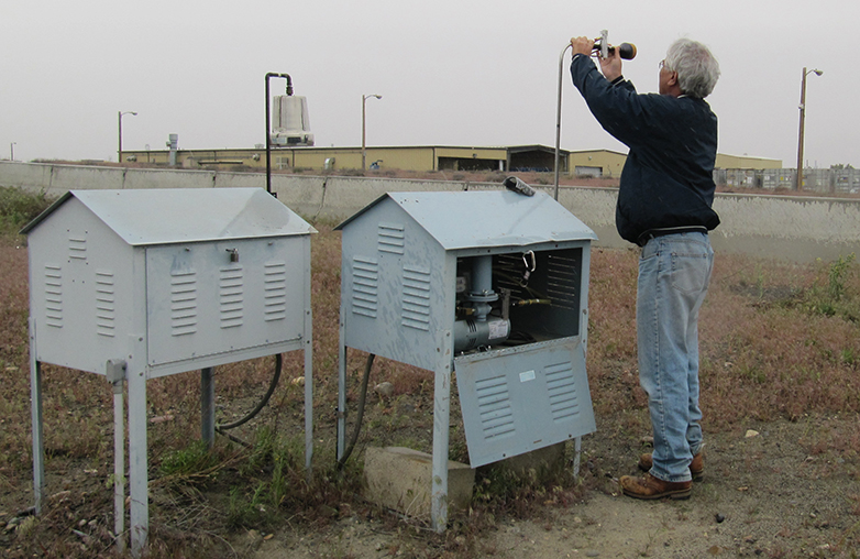 Photo of person examining filters at an air quality monitoring station. The structures that house the equipment are grey, metal structures that resemble small chicken coops.