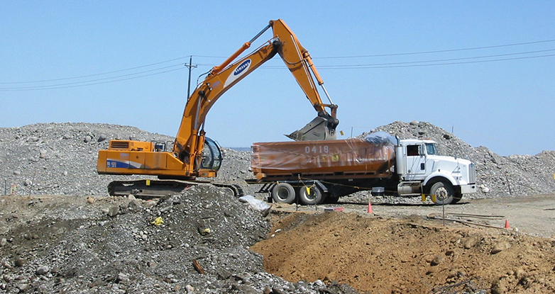 Backhoe dumps dirt into dumptruck at Hanford site.