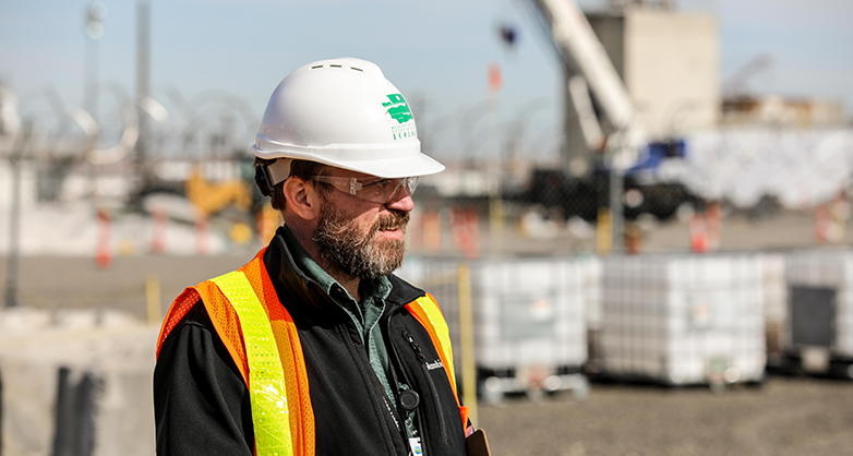 An Ecology employee stands on the Hanford Site in safety gear, with buildings in the background.