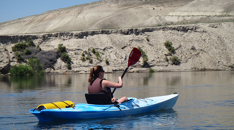A woman in a kayak paddling on the Columbia river.