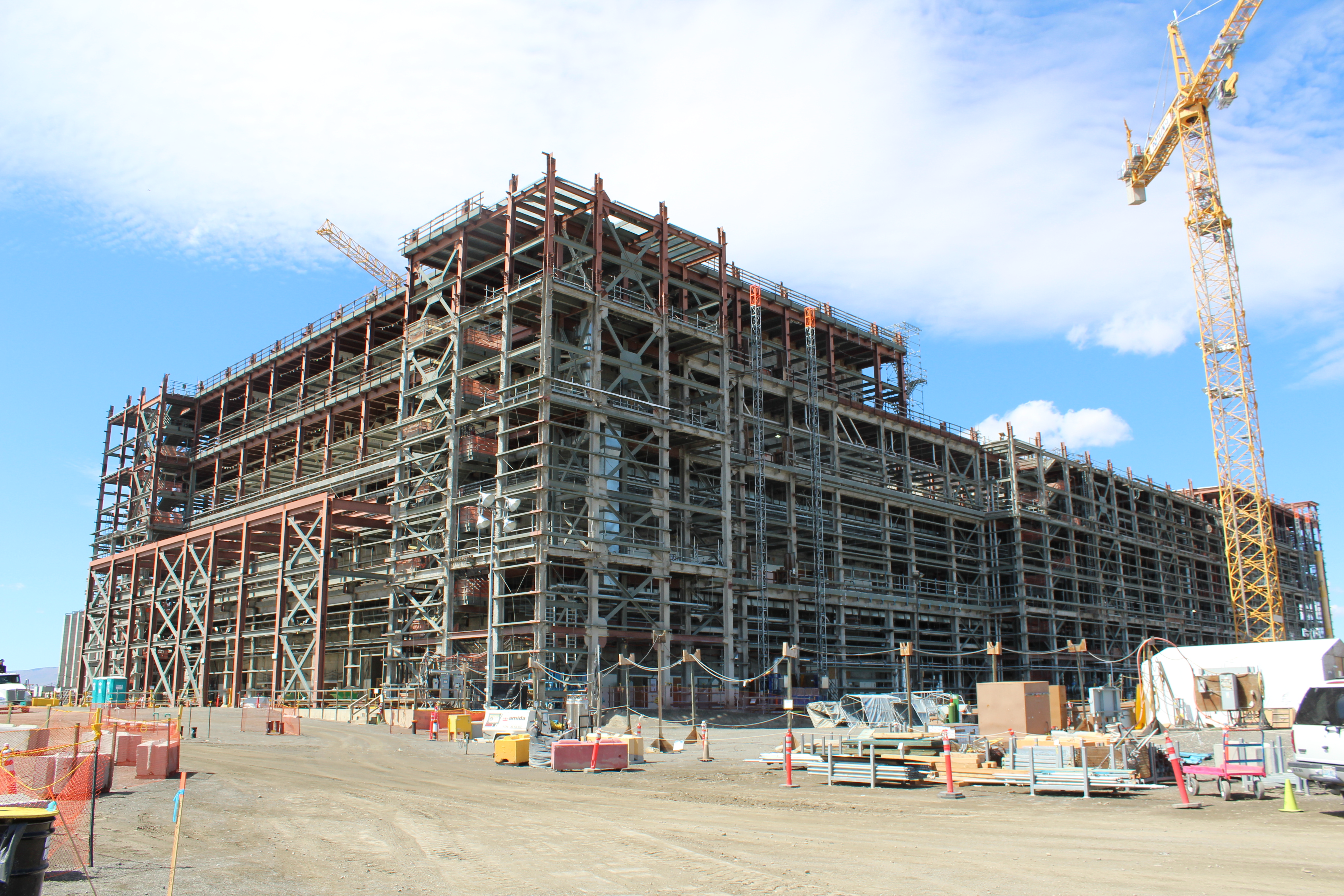 Photo of the Pretreatment Facility at the Waste Treatment Plant. An enormous building still under construction, surrounded by construction equipment, blue sky above.