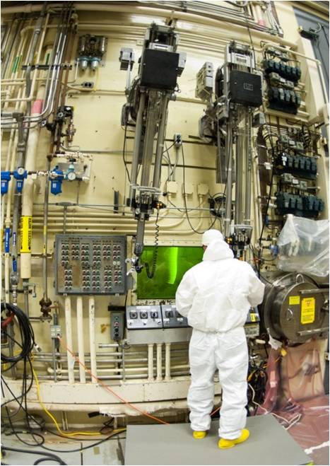 A worker in a white Hazmat suit stands before a large egg like structure with a glowing green window.
