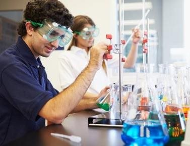 Students perform a chemistry experiment with liquid filled flasks and laboratory equipment