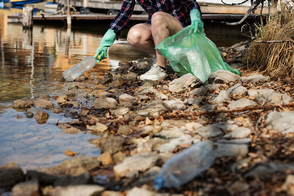 This is a decorative image of a woman picking up littered plastic bottles from a stream.