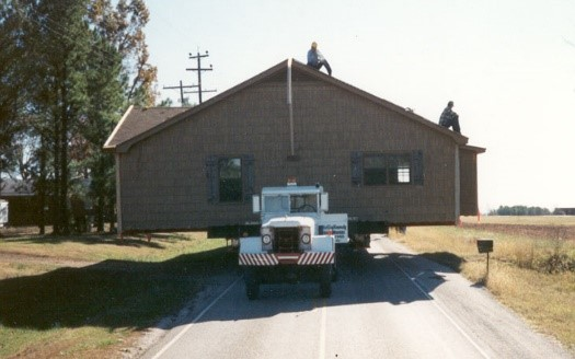 An entire house loaded on a truck being moved down a highway to a new location.