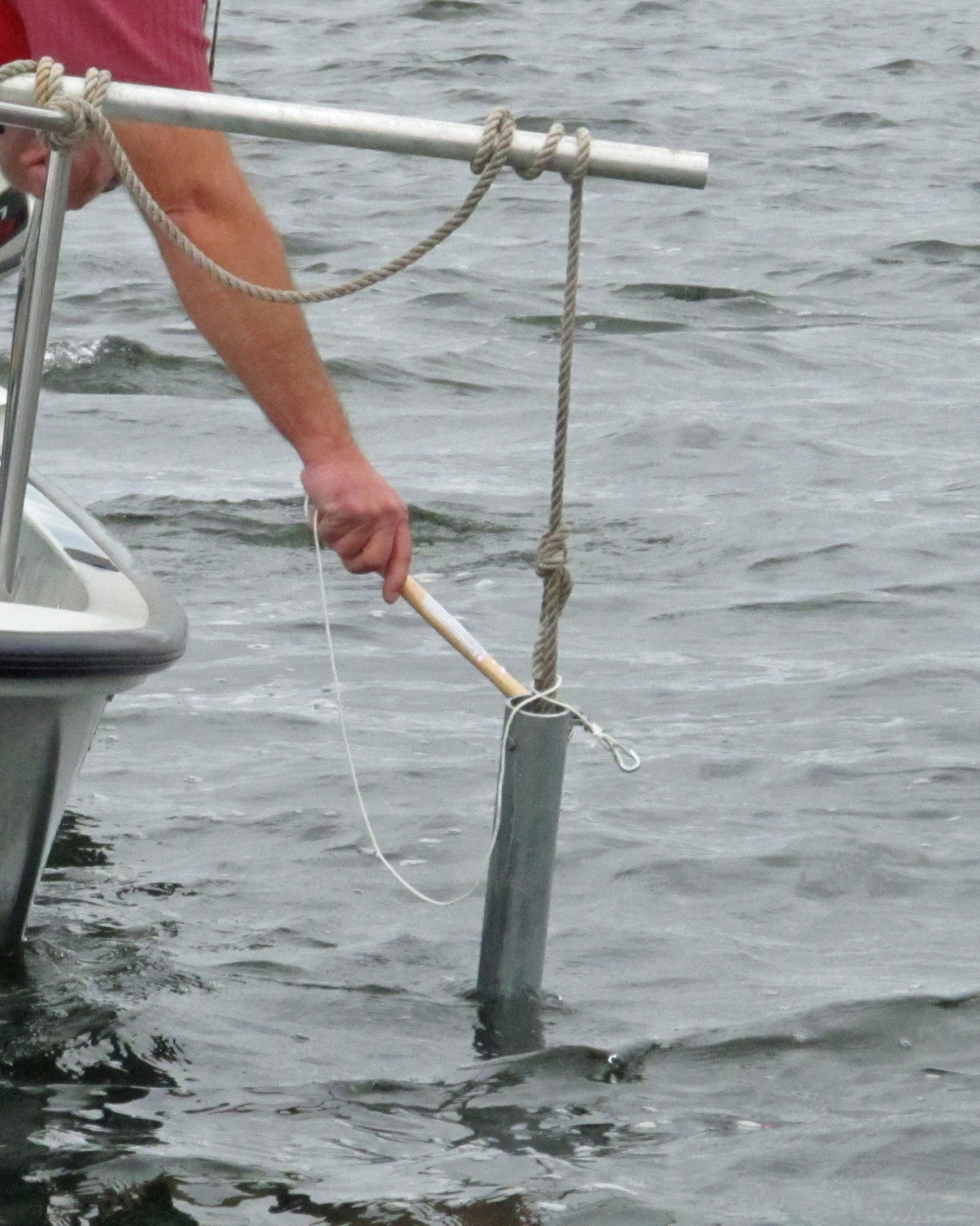 A pipe suspended by cord from a stick is held partly in the water off the side of a small boat, a person's hand holds a metal bar to strike the pipe.