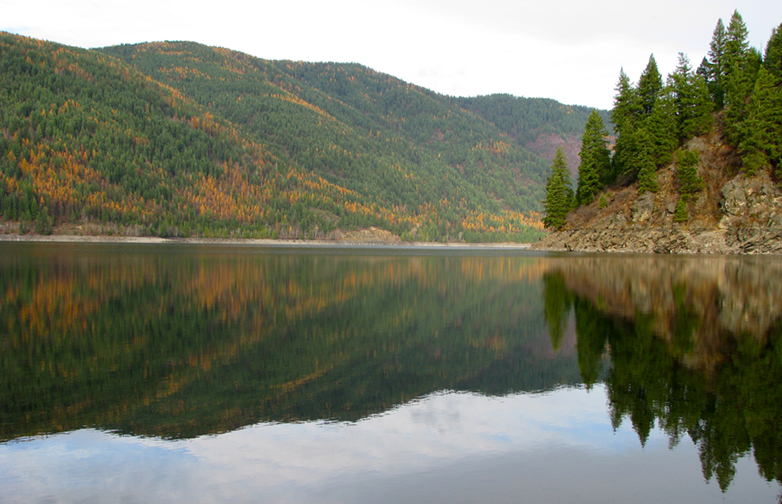 Lake Sullivan in Eastern Washington, surrounded by forested hills that are turning autumn colors