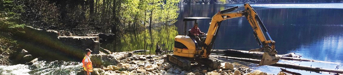 Backhoe moving rocks to repair a dam