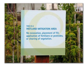 A sign identifying a wetland mitigation area that reads,
