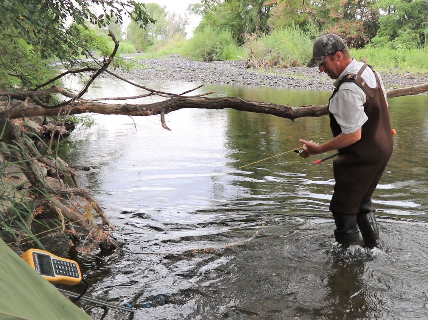 A watershed technician checks instruments in a stream in the Walla Walla River Basin.