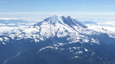 Mt. Rainier with small amounts of snowpack. Fluffy white clouds around summit of mountain.